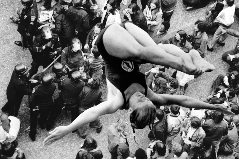 VI TROR VI HUSKER ( # 8 ) - FOTOKOLLAGE AF SIXTEN THERKILDSEN 2013. Pressebillede 1: Konfrontation ved anti-krigs demonstrationen. Pressebillede 2: Olympisk mester springer.